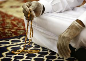 A worshipper wears gloves to prevent the spread of Covid-19 as mosques reopened across Saudi Arabia (Amr Nabil/AP)