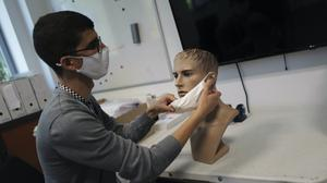 A technician of the French General Armament Directorate analyses public masks in their lab south of Paris (Francois Mori/AP)