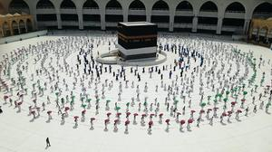 Hundreds of Muslim pilgrims circle the Kaaba while socially distancing (AP)