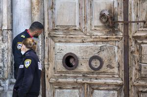 A priest peers from a window in the door of the Church of the Holy Sepulchre in Jerusalem (Ariel Schalit/AP)