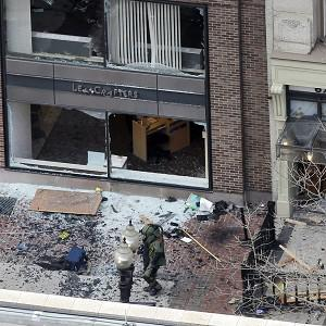 One of the blast sites is examined on Boylston Street near the finish line (AP)