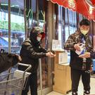 A worker dispenses hand sanitizer to shoppers at the entrance of a supermarket in Wuhan (Chinatopix via AP)