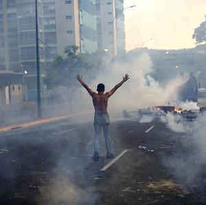 A demonstrator raises his arms toward the Bolivarian National Police (BNP) firing tear gas and a water canon in the Altamira neighborhood of Caracas, Venezuela (AP)