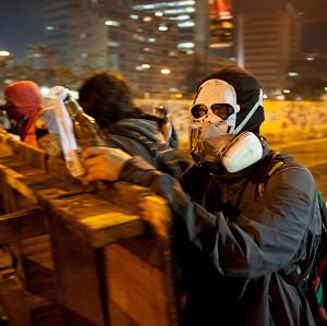 A protester wearing a painter's mask helps build a barricade against the advance of a police water cannon in the Altamira neighbourhood of Caracas, Venezuela (AP)