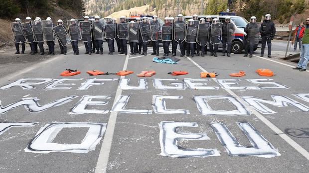 Refugees welcome to EU is painted on a street in front of Austrian police officers in the village of Brenner (AP)