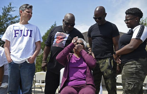 Jessie Hamilton, seated, reacts as she is presented with a cheque to pay off her mortgage as LSU FIJI graduates gather to surprise their former house kitchen staff member and celebrate Jessie Hamilton Day in Baker, Louisiana (Hilary Scheinuk/The Advocate via AP)