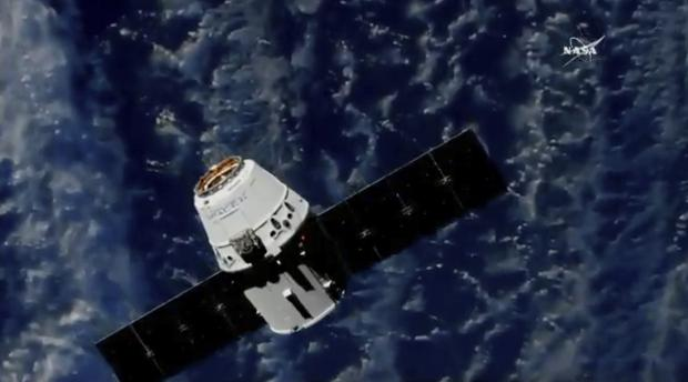 A SpaceX cargo capsule approaches the International Space Station (NASA TV via AP)