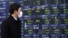 Japan's Nikkei 225 index at a securities firm in Tokyo Friday, March 13, 2020. Shares have plunged in Asia, with Japan's benchmark sinking 10% after Wall Street suffered its biggest drop since the Black Monday crash of 1987. (AP Photo/Eugene Hoshiko)