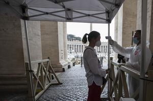 A visitor has her temperature checked in St Peter's Square at the Vatican (Alessandra Tarantino/AP)