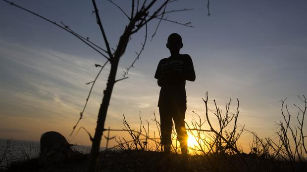 A boy stands on top of the hillside of town of Jeremie, Haiti, which was destroyed by Hurricane Matthew (AP)