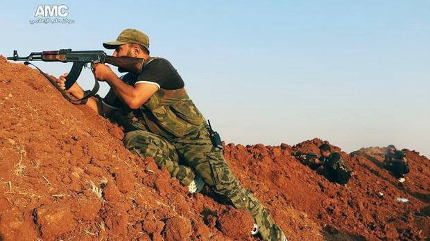 A Free Syria Army fighter aims his weapon during a battle with Islamic State militants in Alepp (AP)