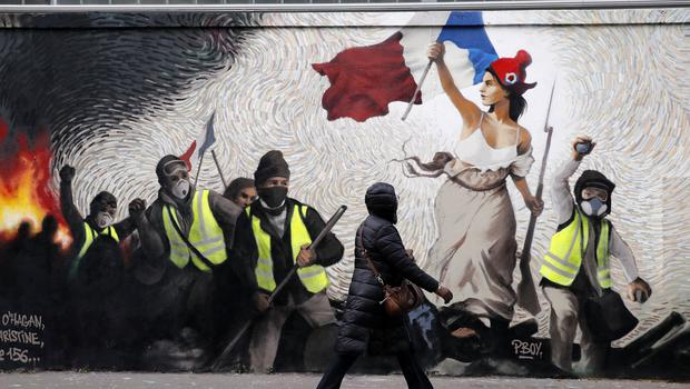 A woman passes a mural by street artist PBOY depicting yellow vest protesters inspired by a painting by Eugene Delacroix, La Liberte guidant le Peuple (Christophe Ena/AP)