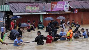 Residents make their way through deep floodwaters after heavy monsoon rains flooded Marikina city, east of Manila (AP)