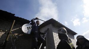 Firefighters try to extinguish a fire at a damaged house after shelling in the town of Donetsk, eastern Ukraine (AP)