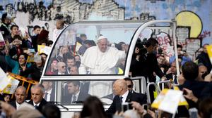 Pope Francis waves from the popemobile in Scampia (AP)