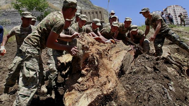 Georgian soldiers clean up an area damaged by flooding near a zoo in Tbilisi, Georgia (AP)