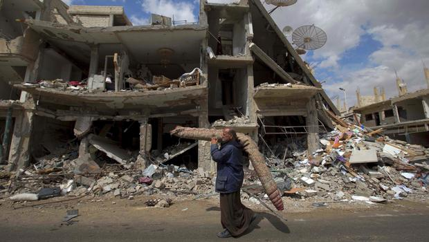 A Syrian man carries a carpet through a devastated part of the town of Palmyra (AP/Hassan Ammar)