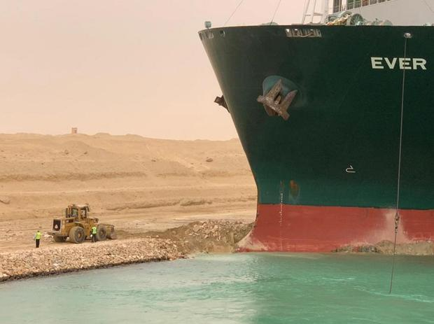 Workers are seen next to a container ship which was hit by strong wind and ran aground in Suez Canal, Egypt March 24, 2021