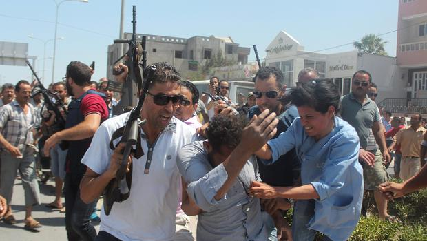 Police officers surround a man suspected of being involved in the attack on a beachside hotel in Sousse, Tunisia