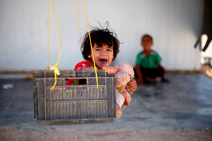 CRYING OUT FOR HELP: A young Syrian refugee on a makeshift swing in Al Zaatari refugee camp in the Jordanian city of Mafraq, near the border with Syria