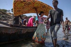 Tigray refugees fleeing the conflict in Ethiopia's Tigray region carry their belongings off a boat after arriving on the banks of the Tekeze River on the Sudan-Ethiopia border. Photo: Nariman El-Mofty/AP Photo