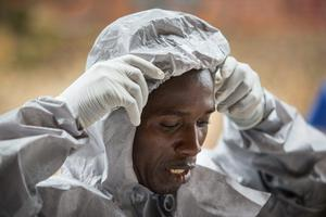 A weary health worker at Kenema General Hospital in Sierra Leone begins to remove his personal protective equipment following a stint inside the hospital's Ebola Isolation Unit. Photo: Mark Condren