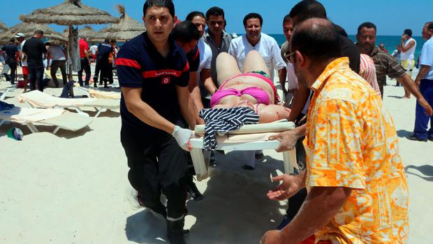 Tunisian medics carry a woman on a stretcher in the resort town of Sousse. Photo: Getty