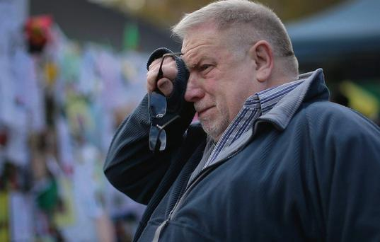 A man weeps as he visits the tribute wall to Nelson Mandela outside the Medi-Clinic Heart Hospital in Pretoria.