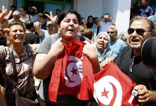 Mohammed Brahmi's daughter Balkis, centre, holds a Tunisian flag as she mourns her father's death in Tunis