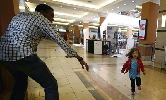 Portia Walton (4) runs towards her rescuer Abdul Haji in an iconic picture from the Nairobi mall siege seen around the world
