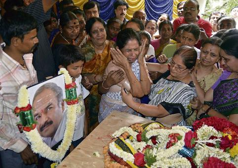 MOURNING: Relatives are bereft next to the body of BN Sudarshan, who was killed in the Westgate shopping mall