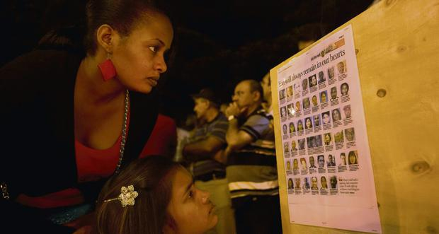 A woman reads a list of the names of those who died, as Kenyans pay their respects in front of the Westgate Mall in Nairobi, Kenya