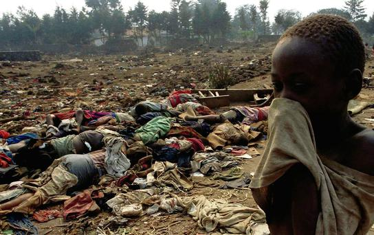 A boy covers his face from the stench of dead bodies during the genocide in Rwanda, 1994 Photo: Corinne Dufka