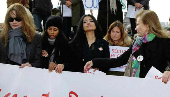 Former French first ladies Carla Bruni-Sarkozy (left) and Valerie Trierweiler (right) stand with politicians and entertainment artists during a 'Bring Back Our Girls' demonstration near the Eiffel Tower in Paris.