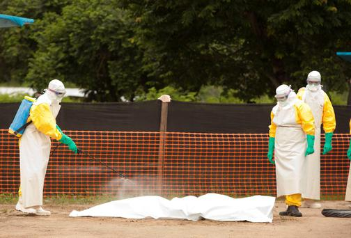 Medical personnel spray disinfectant on a person who died from the Ebola virus in in Foya, Liberia