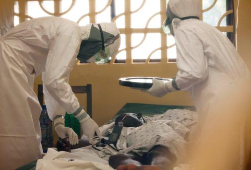 Dr. Kent Brantly, left, treats an Ebola patient at the Samaritan's Purse Ebola Case Management Center in Monrovia, Liberia