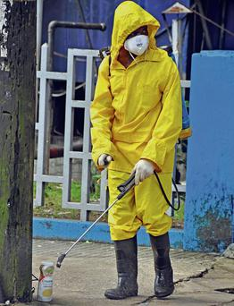 A man sprays disinfectant to stop Ebola spreading in Monrovia, Liberia