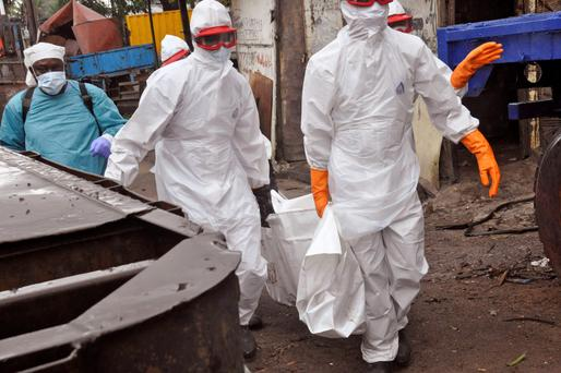 Liberian health workers carry the body of a man that they believe died from the Ebola virus in Monrovia, Liberia.