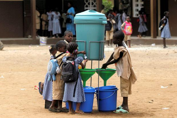 Pupils wash their hands as a preventive measure against Ebola at Anono school in Abidjan,