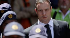 Oscar Pistorius escorted by police officers leaves the high court in Pretoria, South Africa. Photo: AP/Themba Hadebe