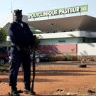 A police officer stands guard outside the quarantined Pasteur Clinic in Bamako November 12. Reuters/Joe Penney