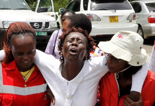 Red Cross staff console a woman after she viewed the body of a relative killed in Thursday's attack on Garissa University, at Chiromo funeral home in Nairobi, Kenya