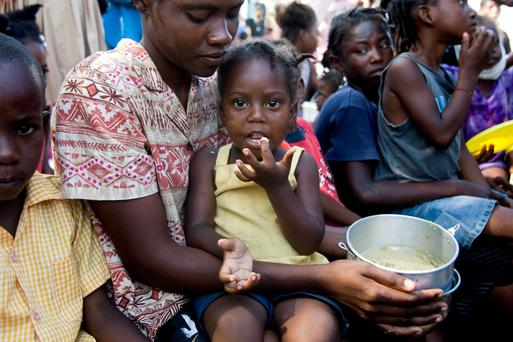 Children dependent on food aid await a meal in Haiti in the aftermath of the 2010 earthquake.