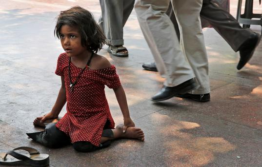 A homeless girl begging on the footpath in New Delhi, India, where the problem of chilhood poverty is particularly acute. Photo: Katy Daigle/AP