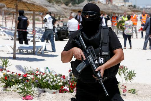 A hooded Tunisian police officer stands guard ahead of the visit of top security officials of Britain, France, Germany and Belgium at the scene of Friday's shooting attack in front of the Imperial Marhaba hotel in Sousse, Tunisa