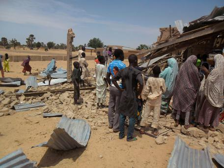 People gather around the Redeemed Christian Church of God after a bomb blast in Potiskum, Nigeria