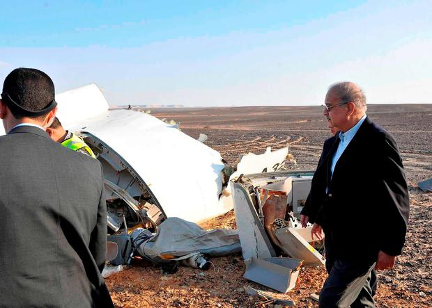 In this image released by the Prime Minister's office, Sherif Ismail, right, looks at the remains of a crashed passenger jet in Hassana Egypt