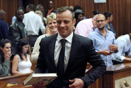 Oscar Pistorius reacts after he was granted bail as he leaves the North Gauteng High Court in Pretoria, South Africa after his bail hearing December 8, 2015. REUTERS/Siphiwe Sibeko