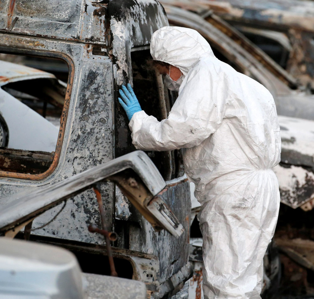 A French police officer inspects burned vehicles at the hotel in Ouagadougou Photo: Reuters