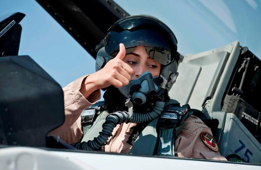 Mariam al-Mansouri, the first Emirati female fighter jet pilot, gives the thumbs up as she sits in the cockpit of an aircraft in United Arab Emirates. She has been held up as a symbol of female empowerment in the Gulf state.